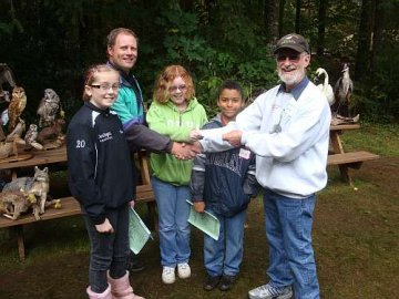 WHAS Education Chair Darrel Whipple presents WHAS's donation for Wake Robin Learning Center to instructor John Gross, representing Longview School District at the site, on Thursday, October 13th, as three fifth graders share the happy moment